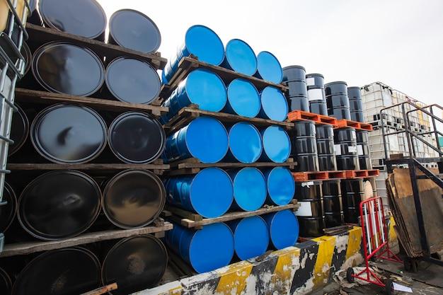 Barili di petrolio blu e neri o fusti chimici impilati orizzontalmente