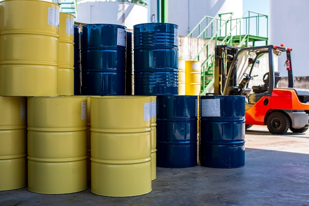 I barili di petrolio blu o i tamburi chimici impilati verticalmente sul carrello elevatore dell'industria si muovono per il trasporto