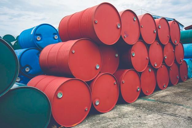 Barili di petrolio verdi e rossi o fusti chimici impilati orizzontalmente