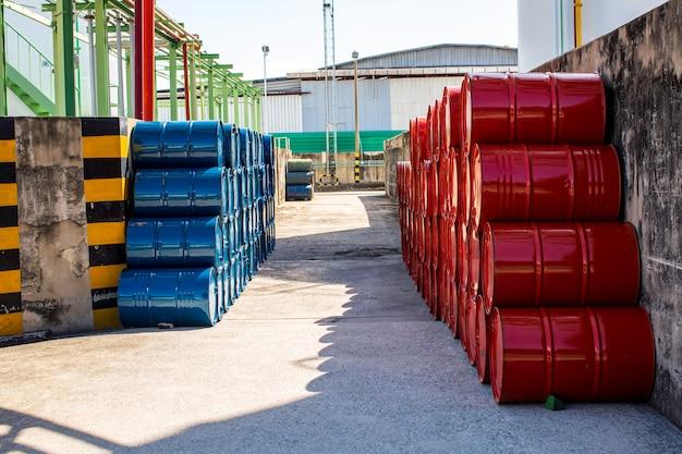 Barili di petrolio rossi e blu o fusti chimici impilati orizzontalmente