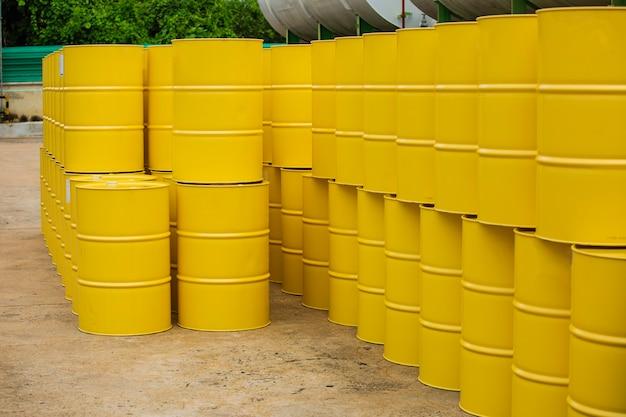 Barili di petrolio gialli o fusti chimici impilati verticalmente.