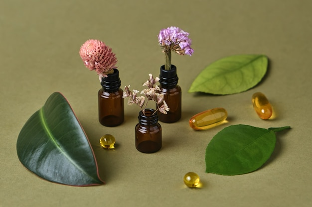 Bottiglie di olio con fiori aromatici, foglie fresche e capsule gialle su sfondo verde oliva