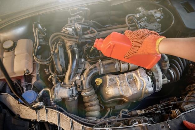 Cambio dell'olio al servizio dell'auto. mano in guanto protettivo con bottiglia di olio