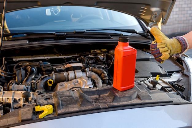 Concetto di cambio olio. maschio a braccetto con la bottiglia dell'olio e il motore dell'auto da vicino