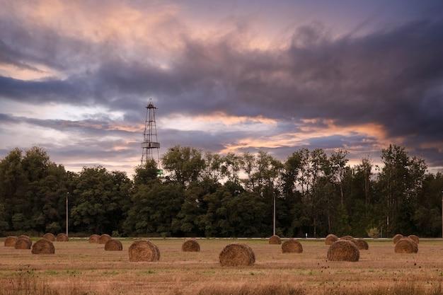 Industria petrolifera. piattaforme petrolifere sullo sfondo di rotoli con fieno, paglia al tramonto. copia spazio.
