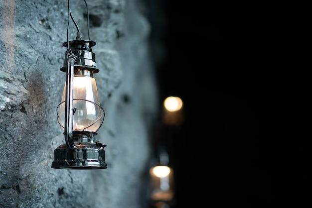 Lampada a olio appesa al muro di pietra della grotta