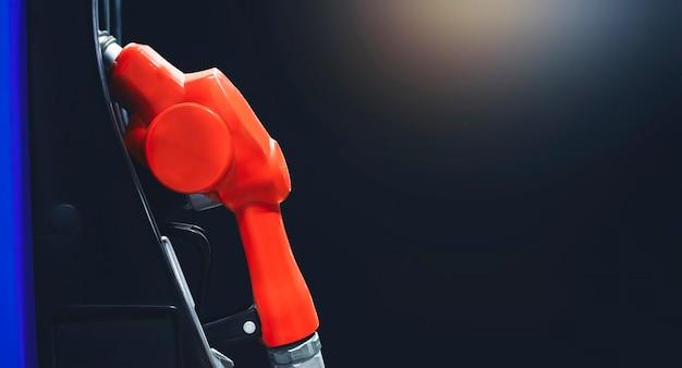 Pompa dell'ugello dell'olio isolata nella stazione di servizio di benzina di notte con sfondo di colore nero e spazio di copia