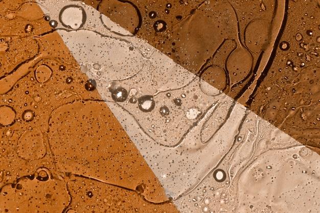 Struttura di caduta di olio sul fondo marrone e beige del colorblock