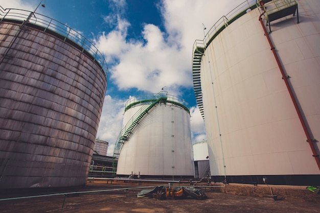 Serbatoio di stoccaggio dell'olio con cielo blu del fondo della conduttura dell'impianto di raffineria di petrolio