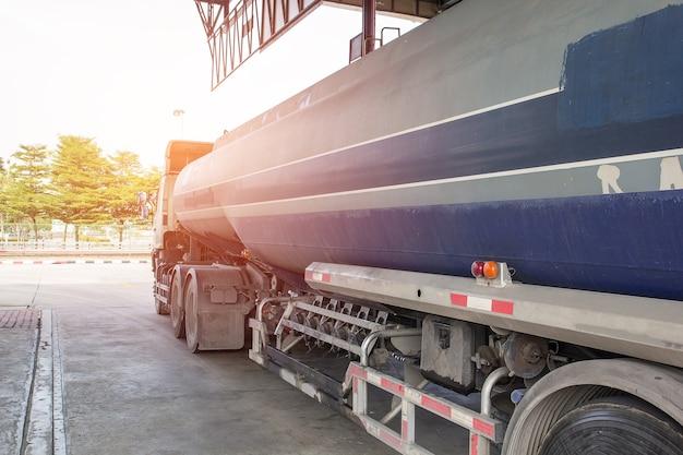 Camion dell'olio rilasciando serbatoi inossidabili di olio combustibile nella stazione di servizio.