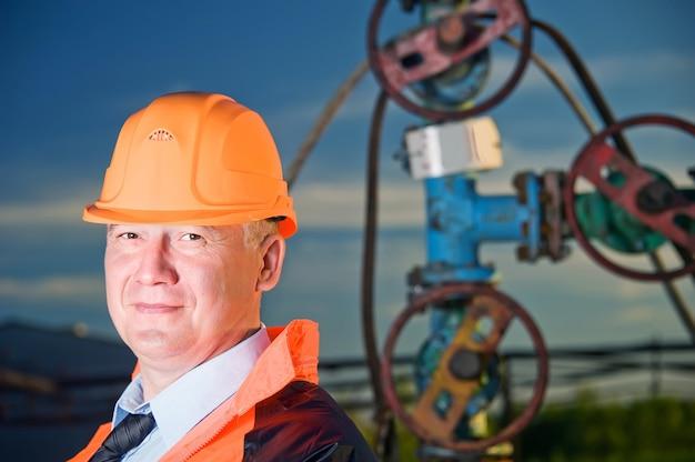 Operaio petrolifero in uniforme arancione e casco sullo sfondo delle valvole, delle tubazioni e del cielo al tramonto.