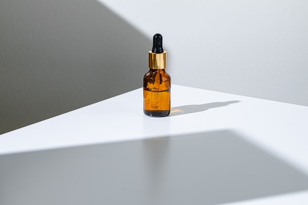 Barattolo di vetro marrone idratante per la cura della pelle grassa con pipetta da vicino