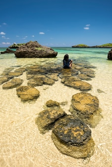 Okinawa ragazza seduta sulle rocce presso la spiaggia di hoshizuna con le sue acque cristalline, isola di iriomote.