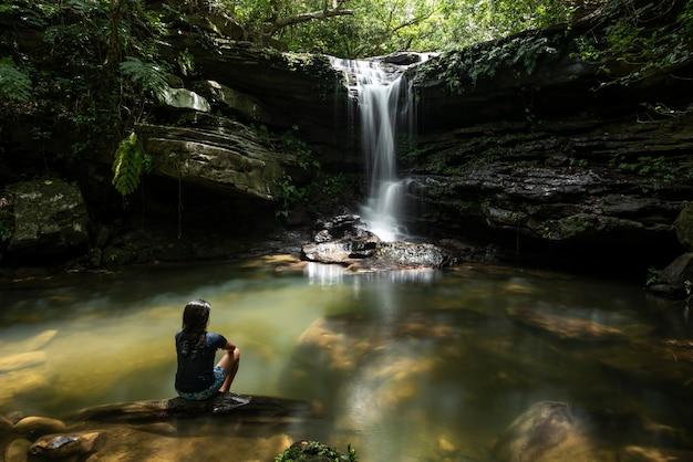 Donna di okinawa che contempla la cascata kura un luogo tranquillo dove rilassarsi con la sua atmosfera serena sull'isola di iriomote yaeyama