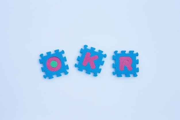 Puzzle di alfabeto okr sulla parete bianca.