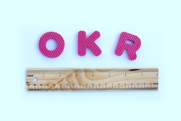 Alfabeto okr con righello in legno sul muro bianco.