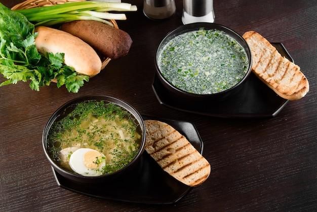 Okroshka, brodo con pasta e uova in banda nera, pane tostato, erbe sul tavolo di legno scuro