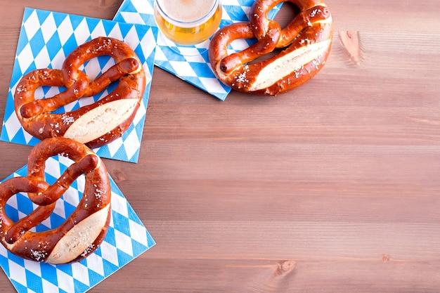 Sfondo oktoberfest con birra e salatini e decorazioni tradizionali bavaresi closeup sul piano del tavolo in legno, banner web, spazio copia