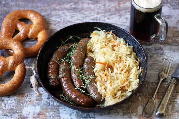 Cibo dell'oktoberfest. salsicce bavaresi calde con crauti in padella. delizioso cibo da festival della birra