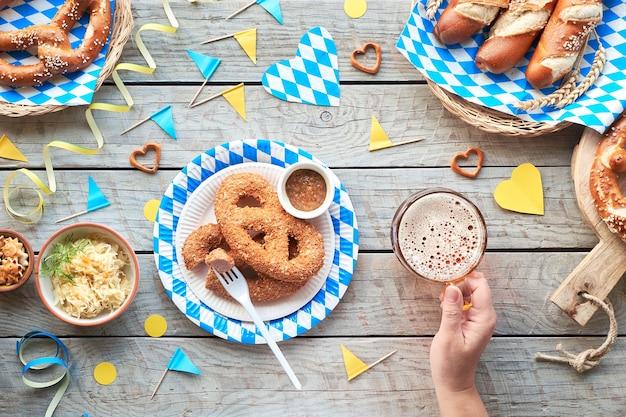 Cibo e birra tradizionali dell'oktoberfest, piatti adagiati su legno con decorazioni bavaresi blu e bianche.