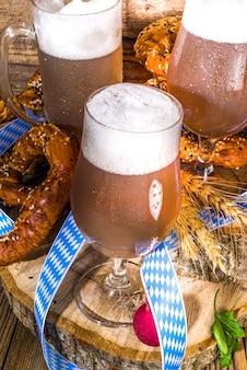 Oktoberfest vari bicchieri da birra e boccali con pretzel, grano e luppolo. menu di bar e pub, sfondo della carta di invito su uno spazio di copia di sfondo in legno