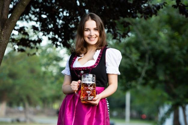Oktoberfest donne che indossano un tradizionale abito bavarese tenendo boccali di birra