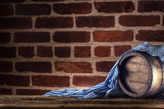 Barile di legno dell'oktoberfest e tovaglia blu su tavola di quercia rustica.
