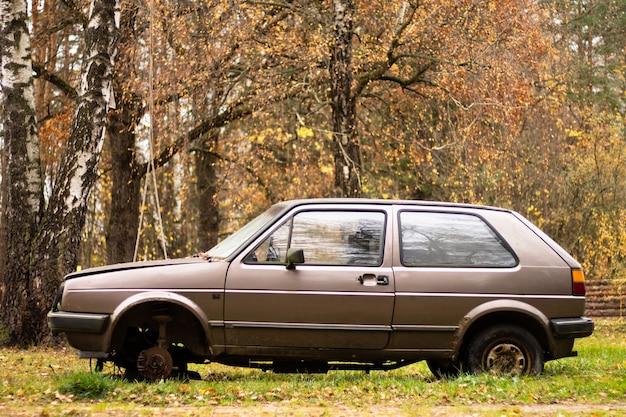 Vecchia automobile beige abbandonata senza una ruota, sullo sfondo della natura autunnale