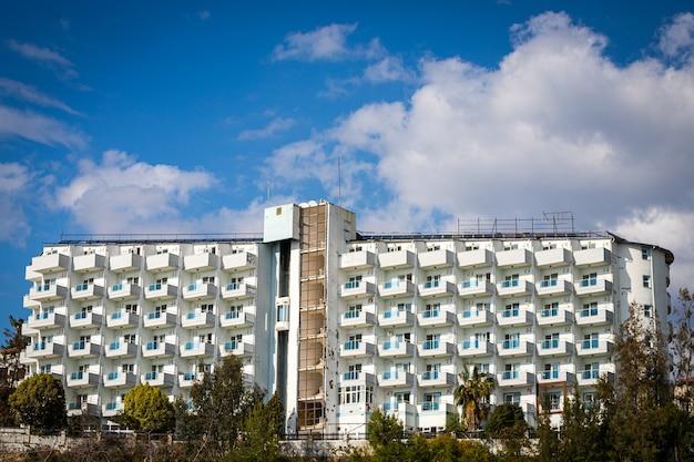 Un vecchio edificio di hotel abbandonato con vetri rotti, un ascensore sulla strada, condizionatori d'aria strappati e insegne in un paese tropicale con palme contro un cielo luminoso