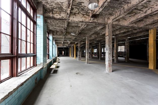 Vecchio interno industriale abbandonato con corridoio e grandi finestre