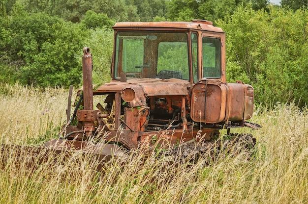 Vecchio trattore abbandonato in un campo ricoperto di erba alta.