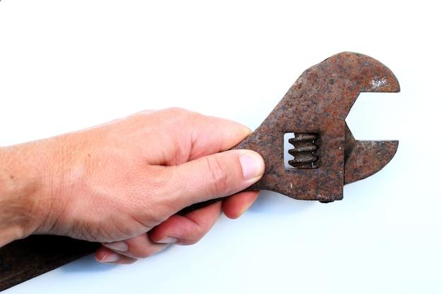 Vecchia chiave regolabile su un primo piano di superficie bianca