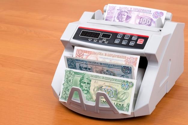 Vecchi soldi albanesi in una macchina da contare
