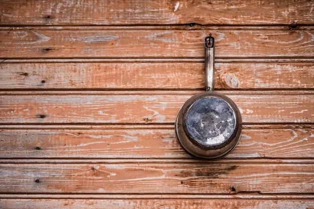 Il vecchio mestolo di alluminio giace su una tavola di legno