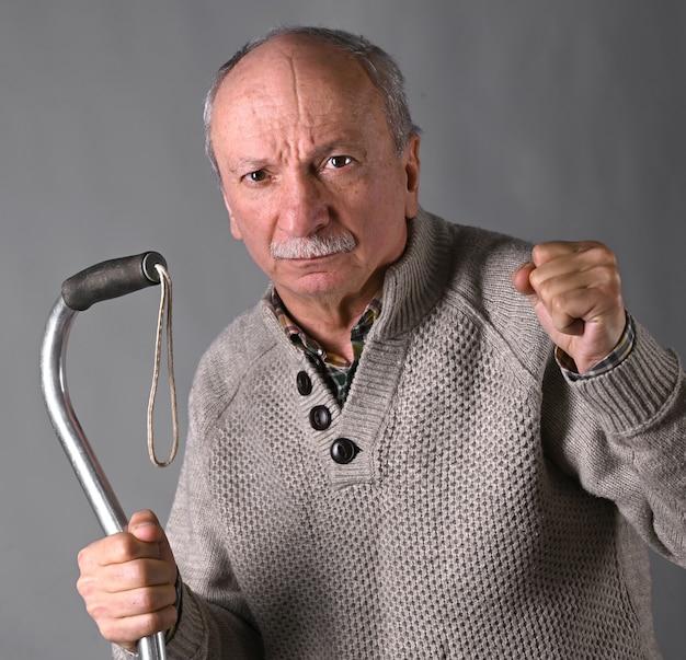 Vecchio arrabbiato che minaccia con un bastone in studio su sfondo grigio