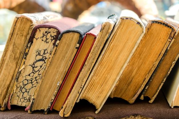 I vecchi libri di antiquariato stanno orizzontalmente in fila. vista frontale. messa a fuoco selettiva