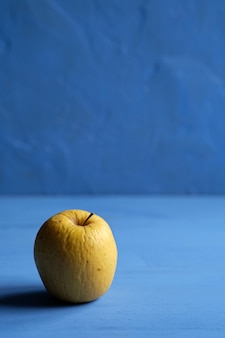 Vecchia mela che inizia a marcire su sfondo blu