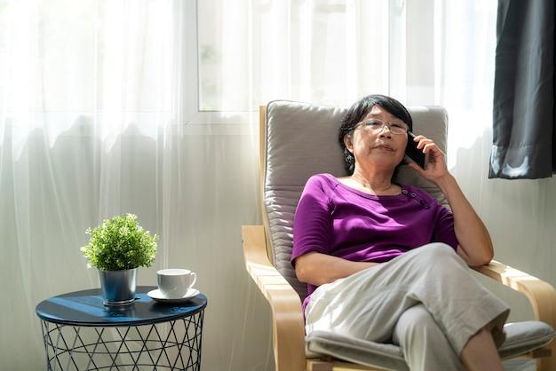 Vecchia donna asiatica di pensionamento sorridente e parlando su smartphone mentre posa sulla poltrona nel soggiorno