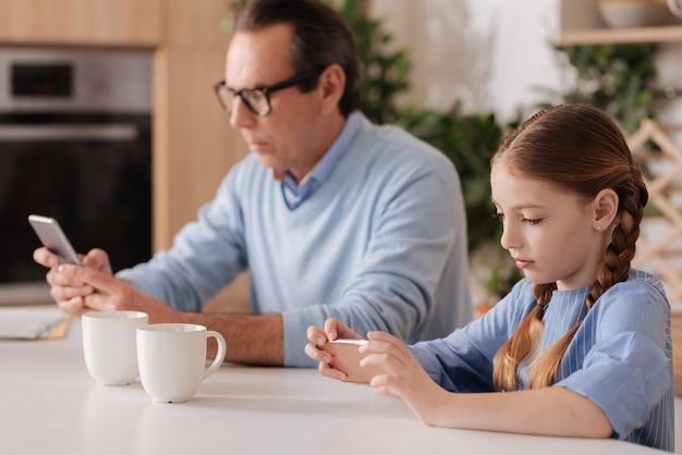 Vecchio uomo concentrato attento seduto a casa e utilizza gli smartphone con la nipote mentre gioca e controlla i profili dei social media