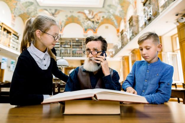 Vecchio uomo con la barba che parla al telefono e che si diverte con la sua piacevole nipotina e nipote adolescenti, leggendo un libro interessante in biblioteca