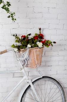 Vecchie bicicletta e fiori vicino al muro di mattoni bianco