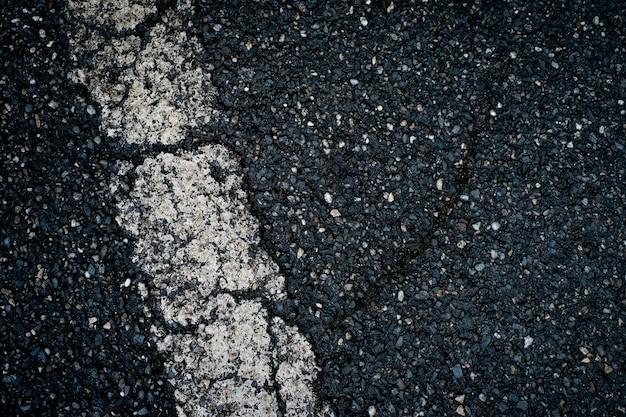 Vecchio asfalto nero con striscia bianca e sfondo di crepe