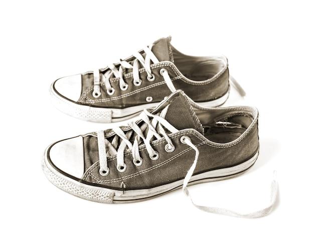 Vecchie scarpe da tennis generiche nere isolate su bianco
