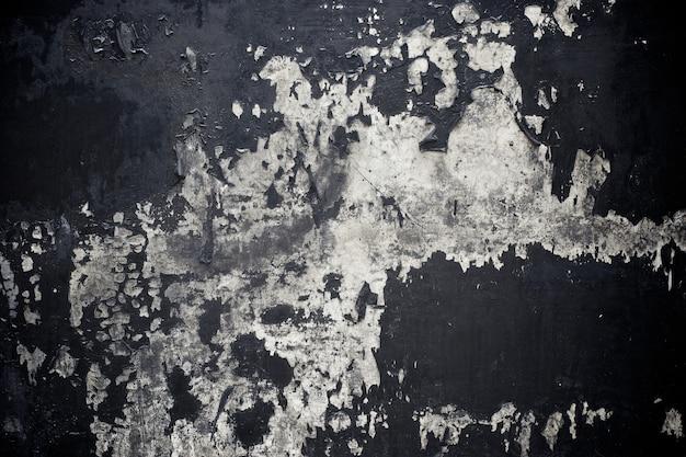 Vecchia struttura della pittura nera che si stacca dal fondo del muro di cemento