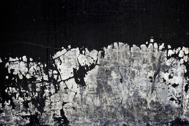 Vecchia struttura di vernice nera che si staccava dal muro di cemento sullo sfondo