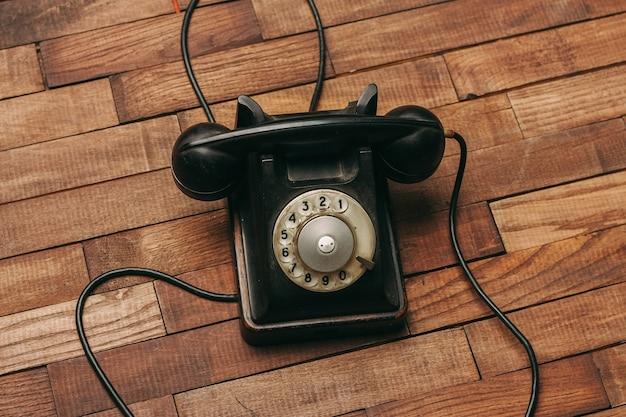 Vecchio telefono nero sul pavimento, vintage