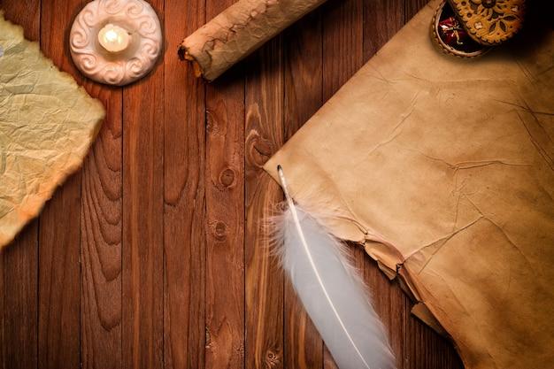 Vecchia carta pergamena vuota e penna su tavola di legno illuminata da candela
