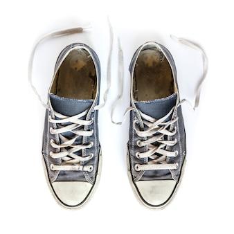 Vecchie scarpe da tennis generiche blu isolate su bianco