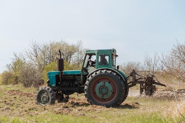 Un vecchio trattore blu ara un campo e coltiva il terreno.