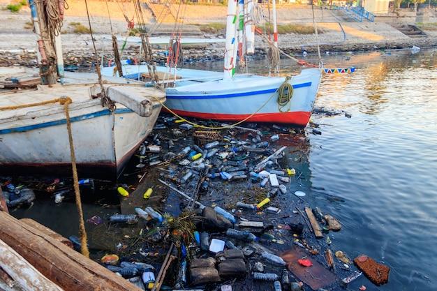 Vecchie barche ormeggiate nel porto sporco. inquinamento del fiume, del mare, dell'acqua dell'oceano con rifiuti, immondizia di plastica. concetto di inquinamento delle coste oceaniche, marittime e fluviali con rifiuti di plastica